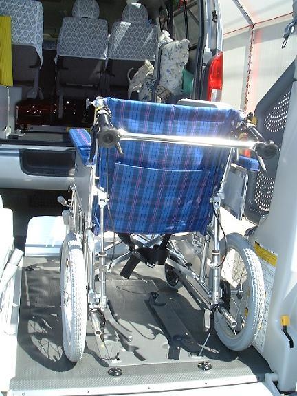 車椅子を固定する様子の写真。